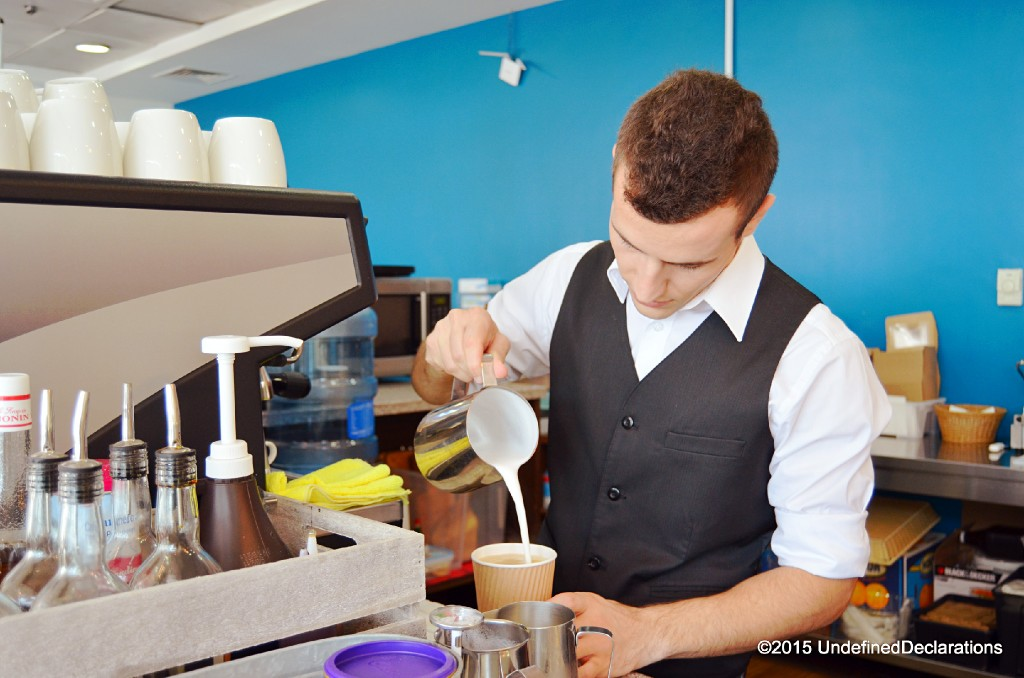 Coffee Barista Koli preparing a latte using RAW coffee beans