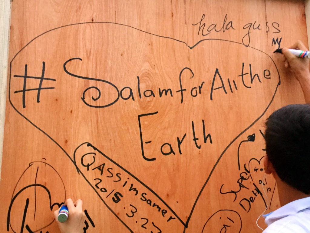 """Children are seen scribbling messages of peace and tolerance on a big board, ahead of the """"Salam Aleikum"""" peace concert at Zabeel Park on Friday evening."""